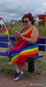 lady on a bench wearing a vivid rainbow dress