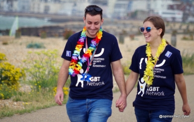 two friends hold hand walking to join Eastbourne Mardi Gras Pride Parade