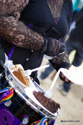 portions of cake sat atop a drum, decorated with rainbow ribbon, being worn by a woman in black lace