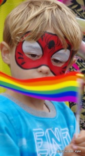 Kids at Pride - young boy holding a rainbow flag, wearing Spiderman face paints. England