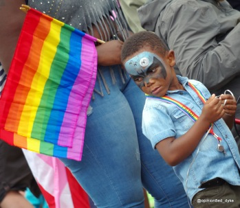 Young BAME boy at Eastbourne Pride with a batman face paint and rainbow flags.