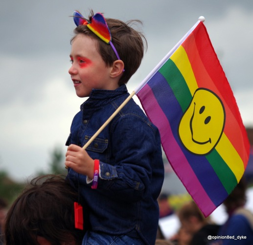 kid at Pride holding a rainbow smile flag