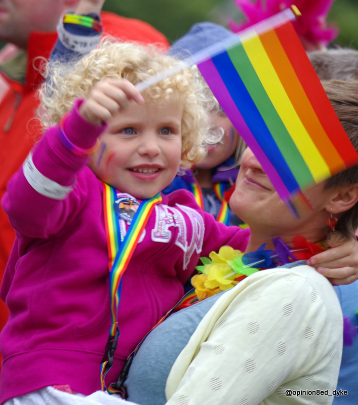 young blonde girl smiling waving rainbow flag LGBT at a 2017 Pride event in England